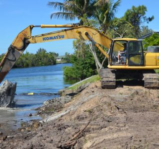 Bubba Williamson digging the water's edge back to allow the new seawall to be positioned.