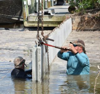 Bubba Williamson tightening a retaining chain across a new section of seawall. There is always an owner of Williamson and Sons on site to construct the new seawall.